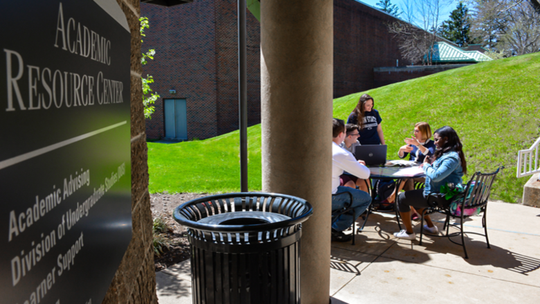 Students crowd around a table to study outside of the Academic Resource Center