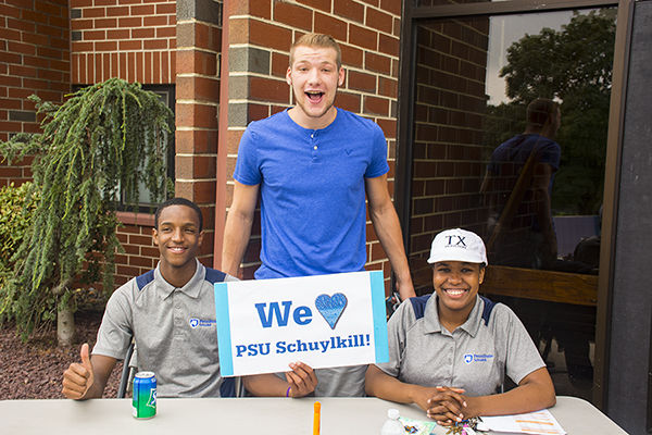 "Three students with a sign that reads ""We heart PSU Schuylkill!"""