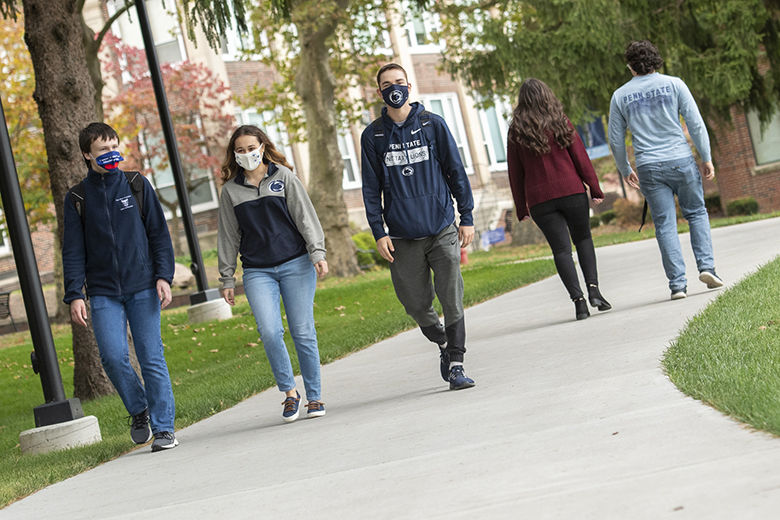 Three students wearing masks and Penn State gear walk toward the Student Community Center.