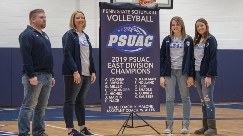 members of the Women's Volleyball team stand with the championship banner.