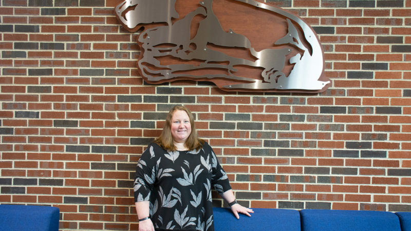 Crystal Shillaci stands under the Nittany Lion in the Student Community Center.