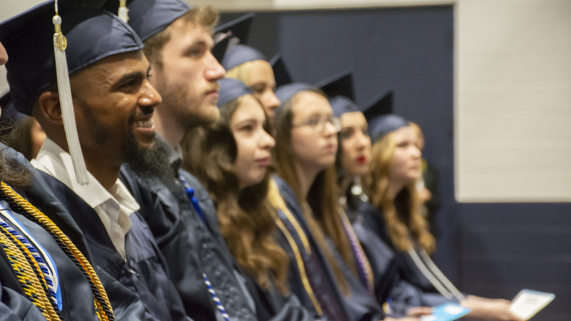 Administration of Justice students grin while Chancellor Patrick Jones confers their degrees in Penn State Schuylkill's gymnasium at the campus' 74th commencement ceremony.
