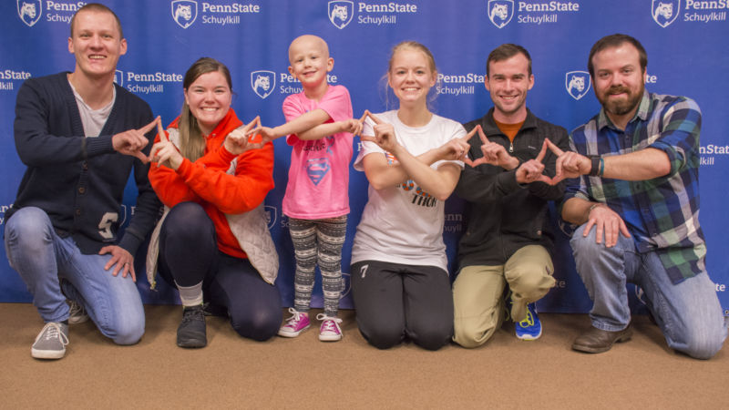 Schuylkill THON dancers pose for a photo with THON child Devin and her father Nick