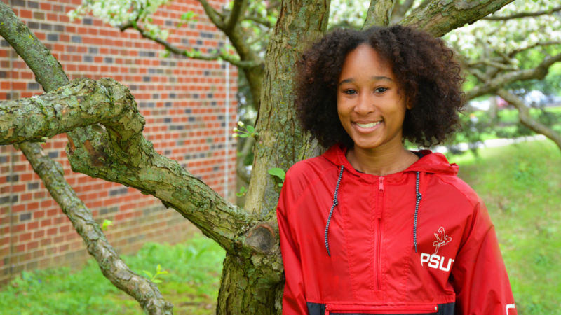 De'Airra Drayton Tilley poses next to a flowering tree on Schuylkill campus