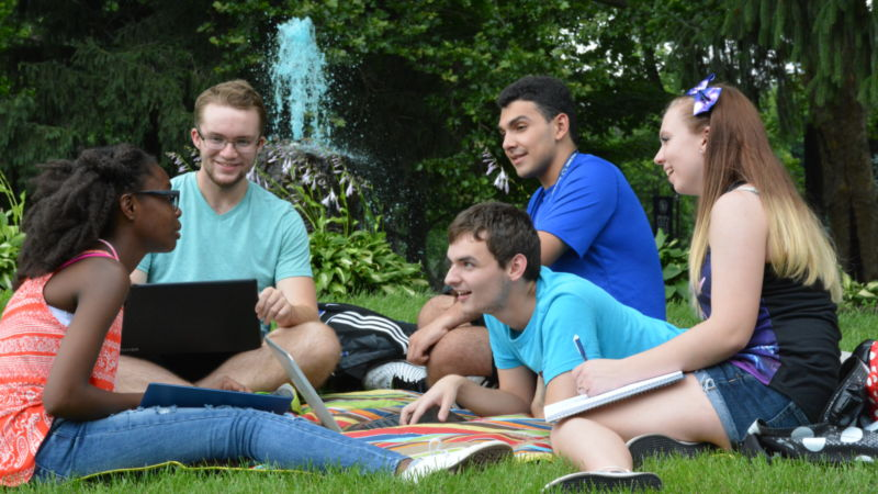 Students conversing around campus fountain