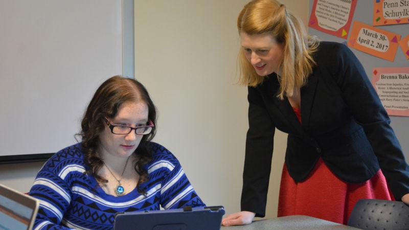 Brenna and Dr. Schrader look over paper