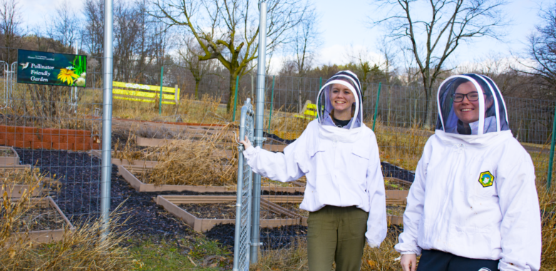 Students Marla and Alyssa stand next to the campus certified pollinator friendly garden in their bee suits.