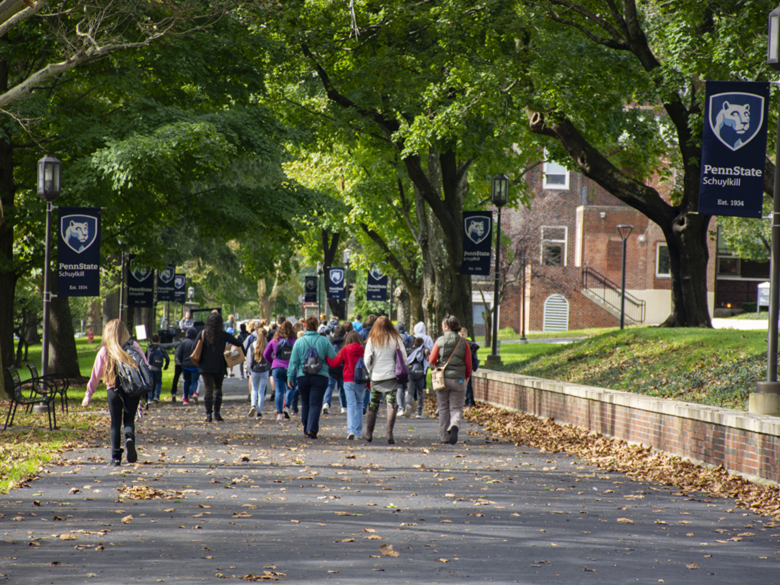 Visiting students walk down Penn State Schuylkill's mall walk.