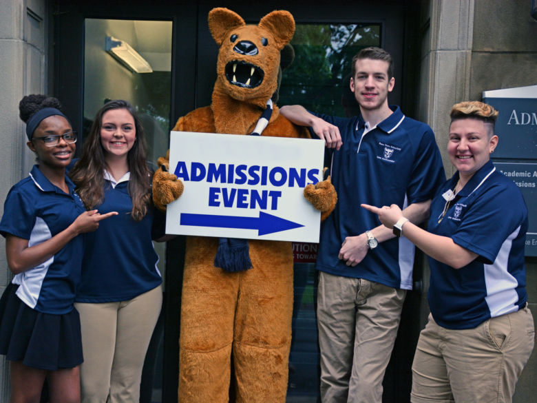Lion ambassadors stand around the Nittany Lion with an admissions event sign