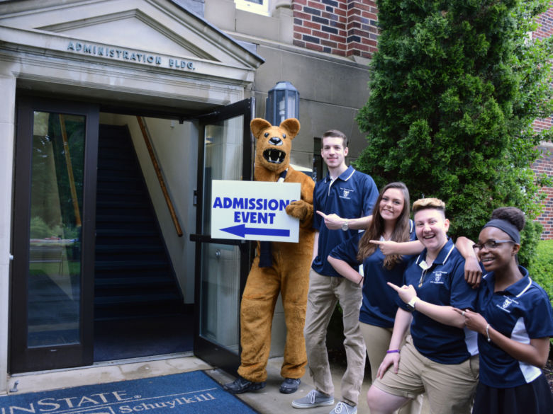 Schuylkill lion ambassadors stand outside the Administration Building with the Nittany Lion mascot inviting prospective students inside.