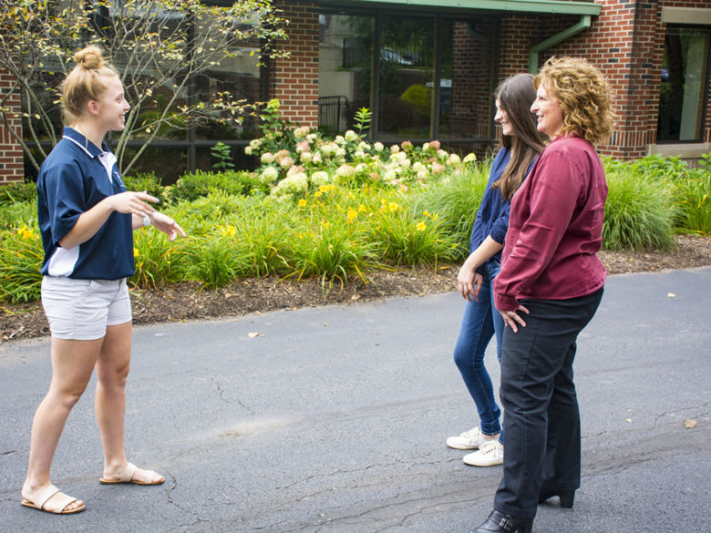 A Lion Ambassador (student tour guide) tells a prospective student and her mother about Penn State Schuylkill outside of the Health & Wellness Building