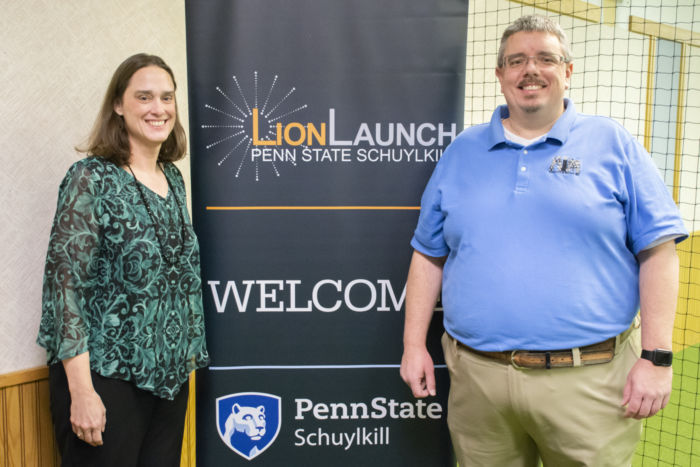 "Darcy Medica, left, stands with her husband Joe, right, with a ""WELCOME"" sign between them featuring Penn State Schuylkill and Penn State Schuylkill LionLaunch logos."