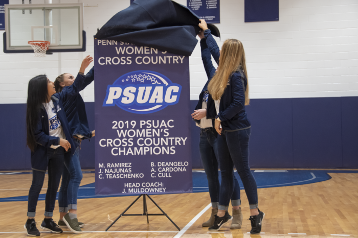 Members of the Women's Cross country team are shown unveiling their championship banner.