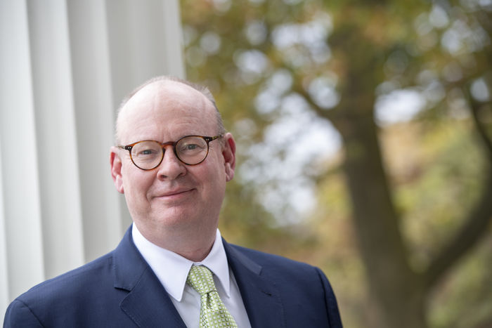 image of Penn State Schuylkill Chancellor Patrick M Jones standing outdoors during the fall with changing leaves in the distance and a white column nearby on the left of the frame