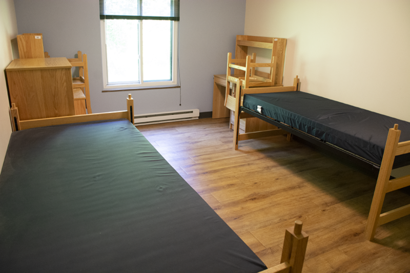 Two twin XL beds and two wooden desks line the walls of a bedroom in the Nittany I Apartments with a window between them.