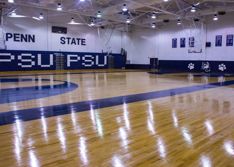Wooden gymnasium floor with reflection of overhead fluorescent lights and bleachers on the side of the wall