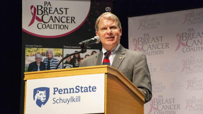 Senator David Argall speaks at a podium with Penn State Schuylkill's logo on the front. A backdrop with the Pennsylvania Breast Cancer Coalition logo is erected behind him.