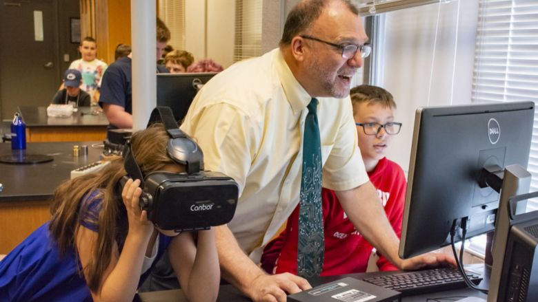 Michael Gallis assists middle schoolers who are trying on VR headsets.