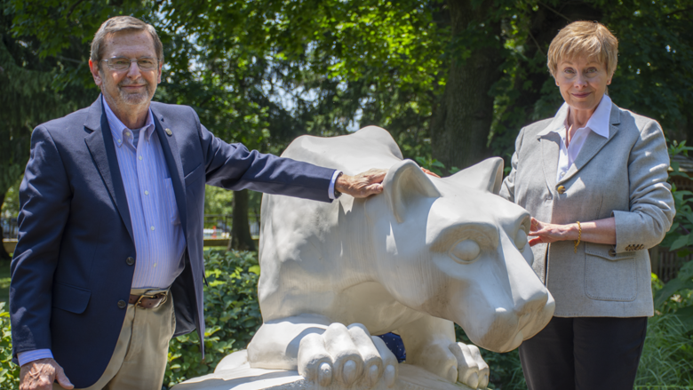 Former Penn State Schuylkill physics professor Dr. Michael Cardamone and his wife, Barbara, pose by Penn State Schuylkill's lion shrine.