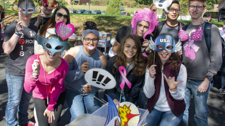 A group of students pose with photo booth props, including superhero garb and pink breast cancer awareness cutouts