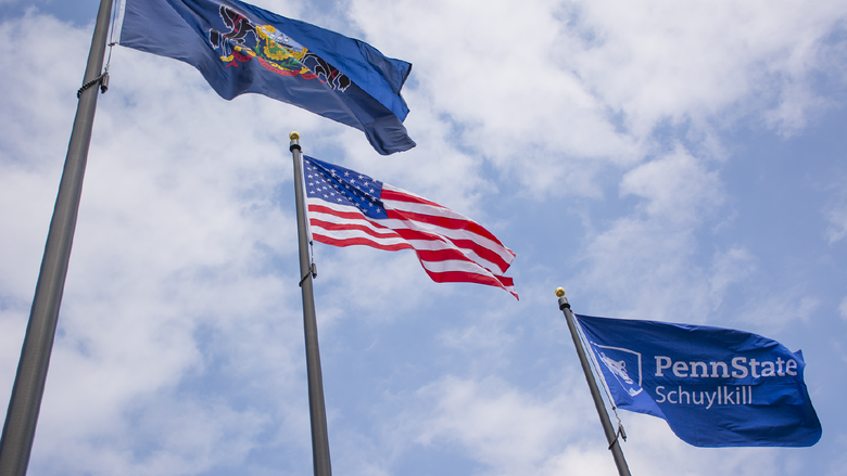 Pennsylvania, U.S., and Penn State Schuylkill flags billow against a blue sky with bright white clouds