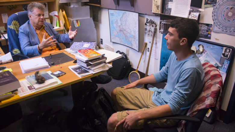 Dr. Cantalupo sits in his eclectic office speaking to a student