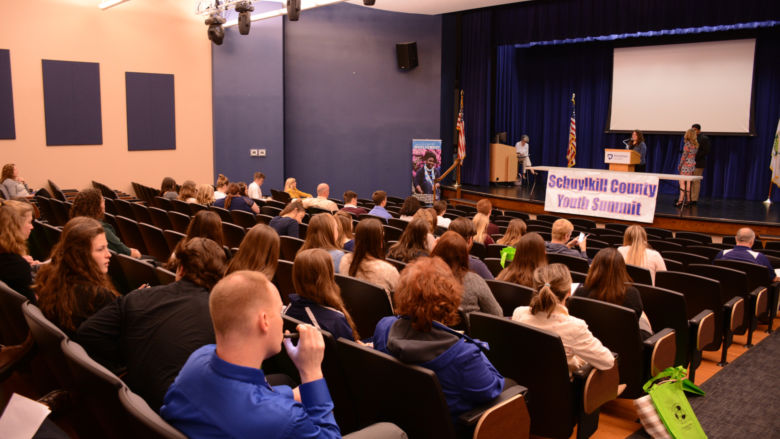Students from 15 area schools listen to students speak at the podium.