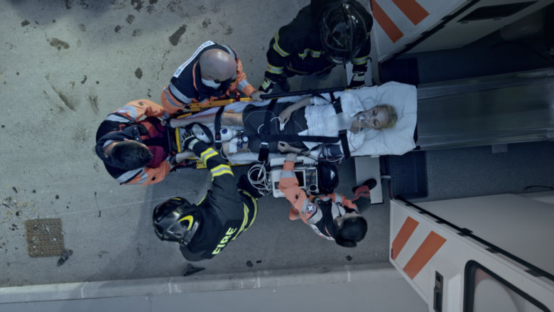 First responders lift and overdose victim into the back of an ambulance