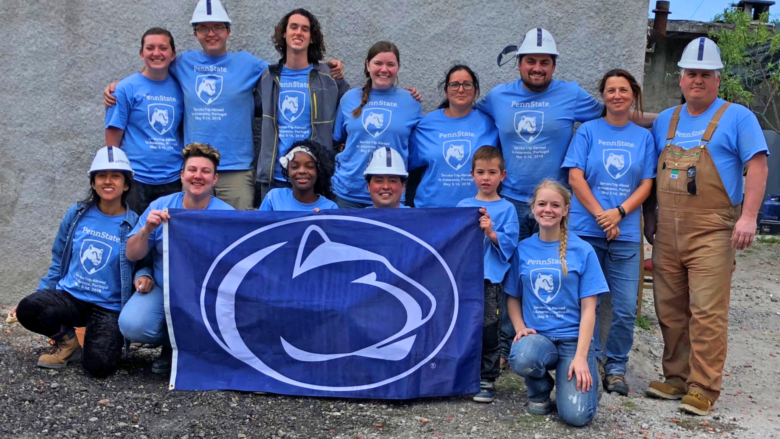 A group of Penn Staters proudly pose in front of their Portugal-based Habitat for Humanity build site.