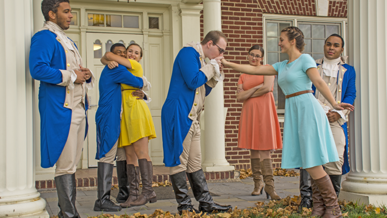 Seven students stand in front of Schuylkill's Kiefer-Jones Building, dressed in theatre production costume.