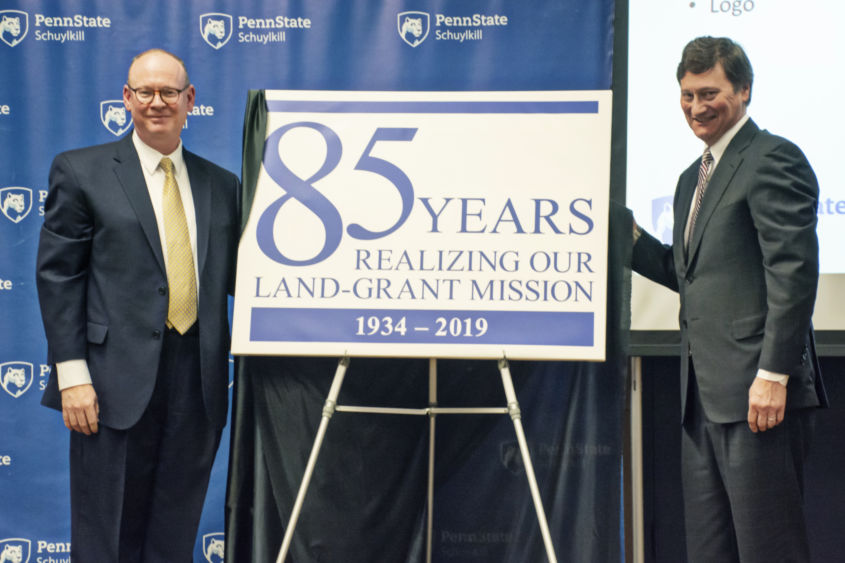 Chancellor Patrick Jones and Schuylkill advisory board member Richard Wiest unveil the 85th anniversary logo