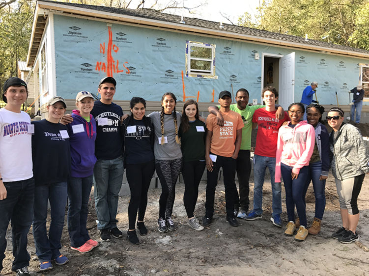 A group of Schuylkill campus student volunteers take a break to pose for a photo in front of their Habitat for Humanity job site.