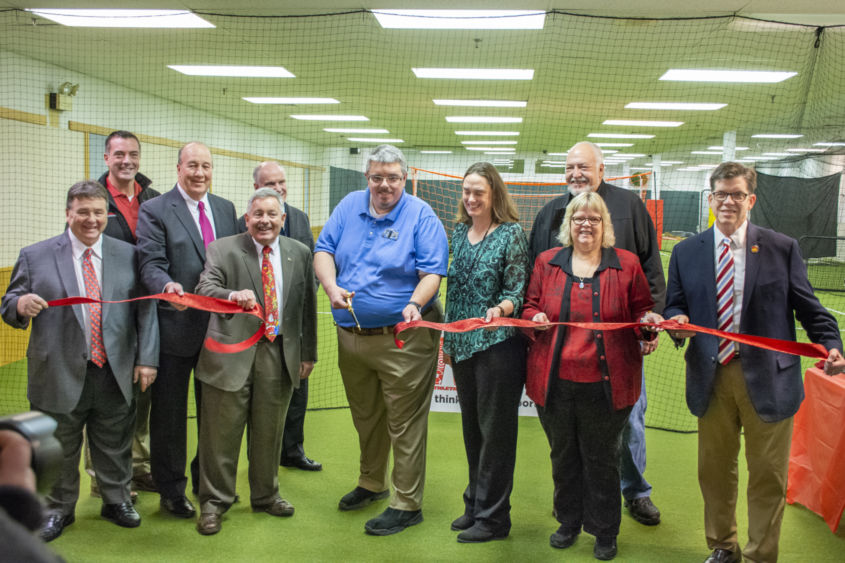 Several people stand on turf grass in a line while holding a red ribbon. Joe Medica stands in the center holding scissors to cut the ribbon.